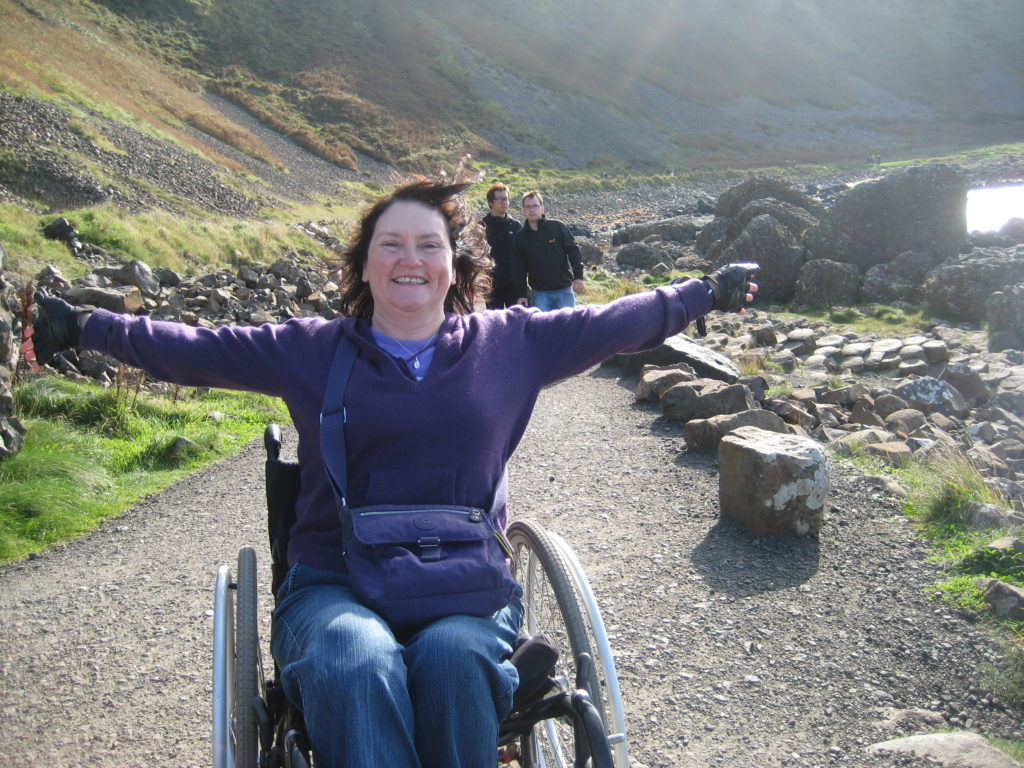 A wheelchair user with arms spread out on a mountain path
